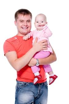 Gelukkige jonge vader die met aantrekkelijke glimlach zijn baby op handen houdt