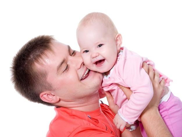 Gelukkige jonge vader die met aantrekkelijke glimlach zijn baby vasthoudt