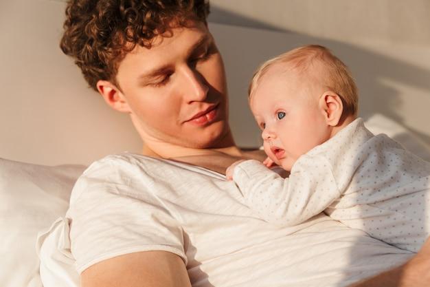 Gelukkige jonge vader die met zijn zoontje aan het spelen is terwijl hij thuis in bed ligt, omarmen