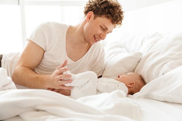 Gelukkige jonge vader die met zijn zoontje aan het spelen is terwijl hij thuis in bed ligt, omarmt