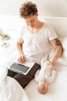 Gelukkige jonge vader die met zijn zoontje speelt terwijl hij op een laptopcomputer werkt en in bed ligt