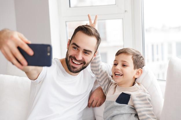 Gelukkige jonge vader die plezier heeft met zijn zoon en selfie maakt op smartphone terwijl hij thuis op de bank zit