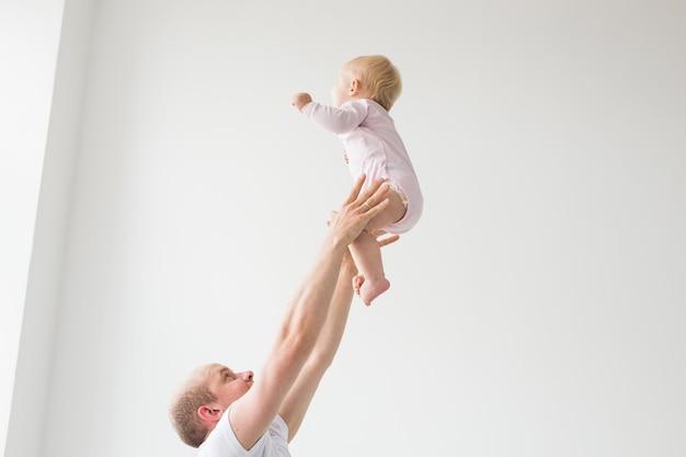 Gelukkige jonge vader die schattige baby hoog in de lucht opheft, samen met tijd doorbrengt en geniet