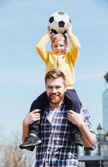 Gelukkige jonge vader die zijn zoontje op schouders vervoert