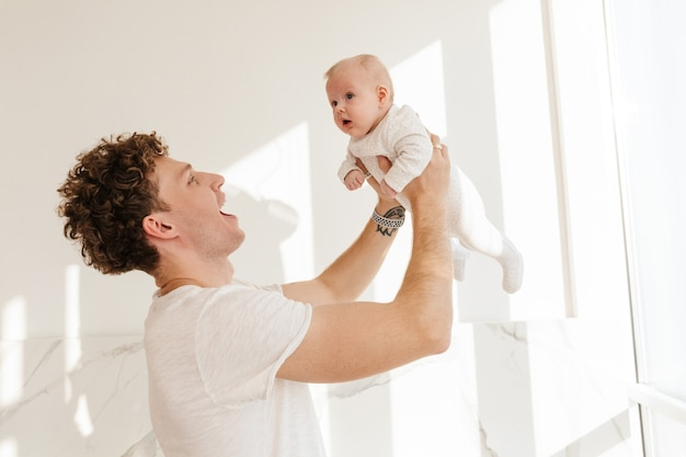 Gelukkige jonge vader die zijn zoontje vasthoudt terwijl hij binnen staat te spelen