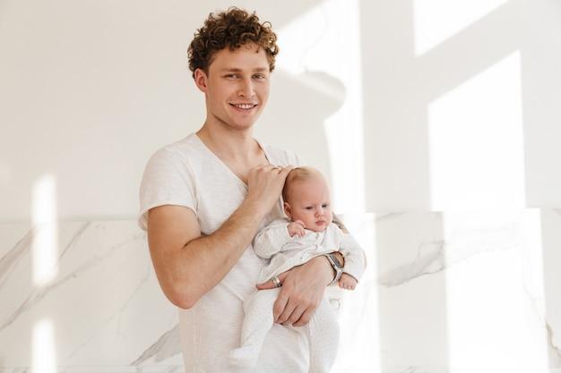 Gelukkige jonge vader die zijn zoontje vasthoudt terwijl hij binnen staat