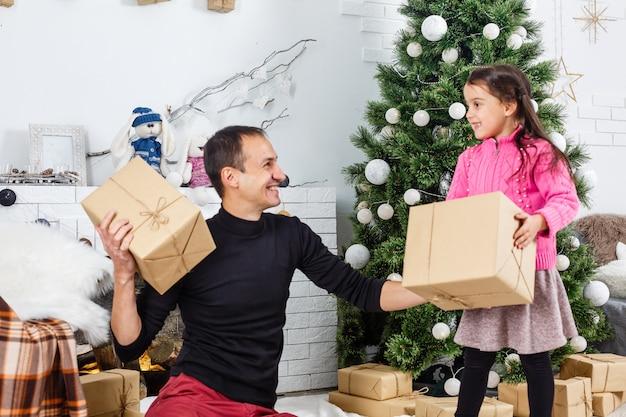 Gelukkige jonge vader en zijn dochter thuis met kerstboom