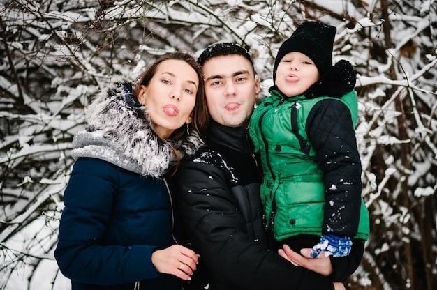 Gelukkige jonge vader, moeder en kinderen jongen, zoon tonen tong in het winterpark.