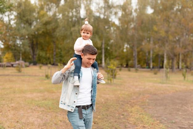 Gelukkige jonge vader op een wandeling met dochtertje op zijn nek