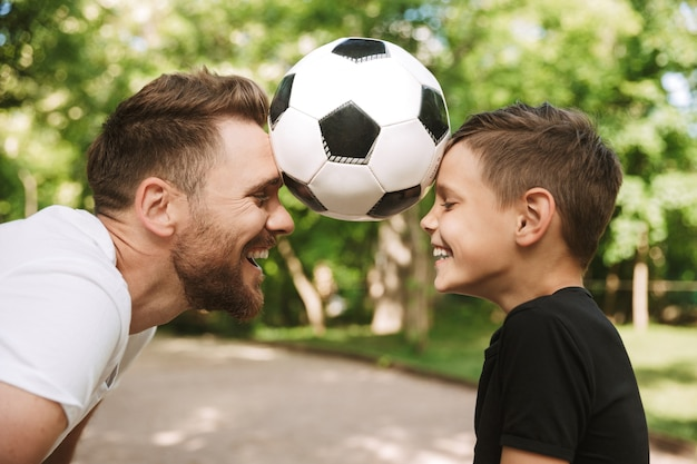 Gelukkige jonge vader veel plezier met zijn zoontje met voetbal