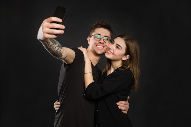Gelukkige jonge verliefde paar selfie maken en glimlachen terwijl staande tegen zwarte achtergrond