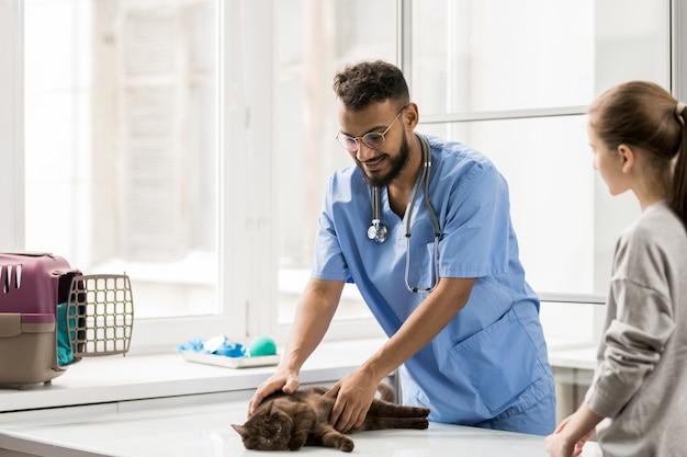 Gelukkige jonge veterinaire arts in eenvormige kinderboerderij kat terwijl het raadplegen van meisje in zijn klinieken