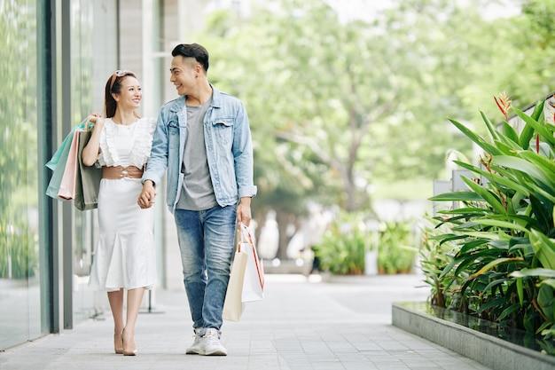 Gelukkige jonge vietnamese paar hand in hand tijdens het wandelen in de straat na het winkelen