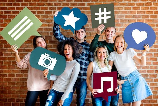 Gelukkige jonge volwassenen die gedachte bel met sociale media conceptenpictogrammen houden