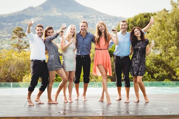 Gelukkige jonge vrienden die dranken hebben bij zwembad en van vakantie genieten