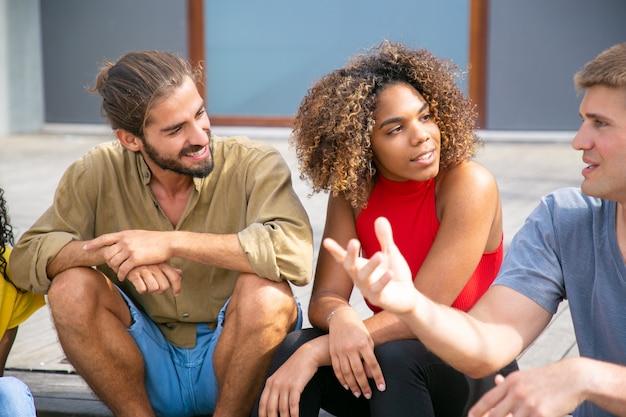 Gelukkige jonge vrienden die in openlucht spreken