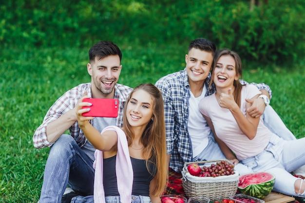 Gelukkige jonge vrienden die picknick in het park hebben. ze zijn allemaal blij en hebben samen plezier.