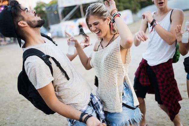 Gelukkige jonge vrienden die plezier hebben op muziekfestival
