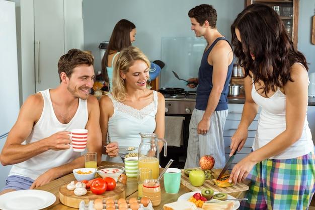 Gelukkige jonge vrienden die voedsel in keuken koken