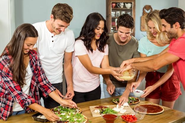 Gelukkige jonge vrienden die voedsel in keuken thuis koken
