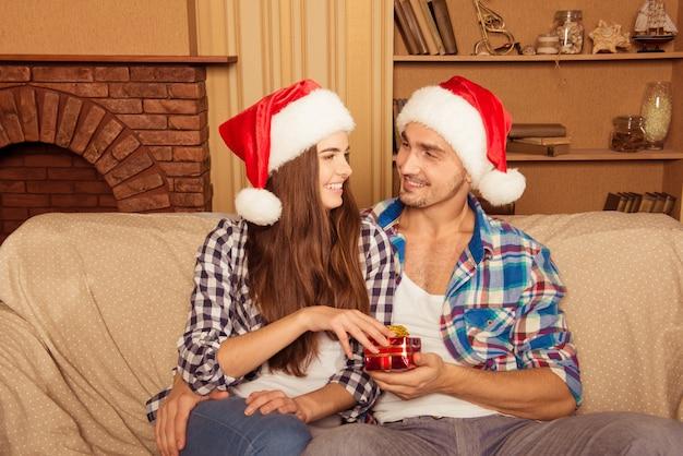 Gelukkige jonge vrienden in santahoeden die kerstmishoed geven