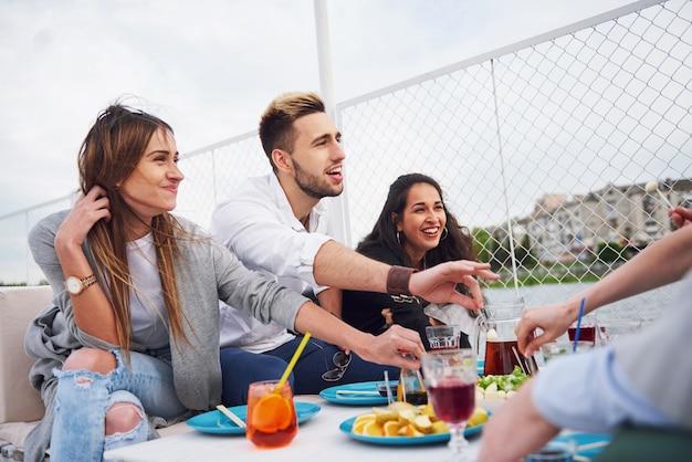 Gelukkige jonge vrienden zaten aan een tafel en hadden een picknick buiten.