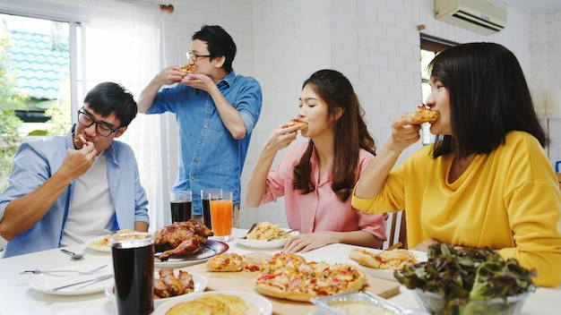 Gelukkige jonge vriendengroep die thuis lunch heeft. azië familiefeest pizza eten en lachen genieten van maaltijd zittend aan de eettafel samen thuis. viering vakantie en saamhorigheid.