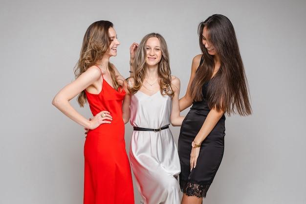 Gelukkige jonge vriendinnen in zijden jurken knuffelen en poseren in de, geïsoleerd op grijze muur
