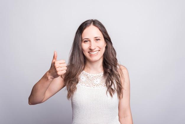 Gelukkige jonge vrolijke vrouw die duim omhoog gebaar toont en de camera bekijkt