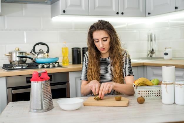 Gelukkige jonge vrouw bereidt zich voor op het doen van fruitsalade voor een dieet in de keuken, gezonde voeding. dieet concept.