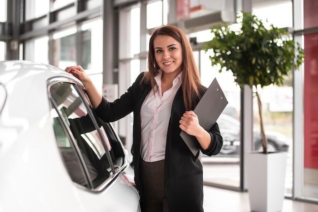 Gelukkige jonge vrouw bij autodealer