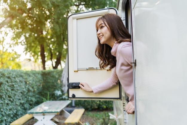 Gelukkige jonge vrouw bij raam van een camper rv busje camper