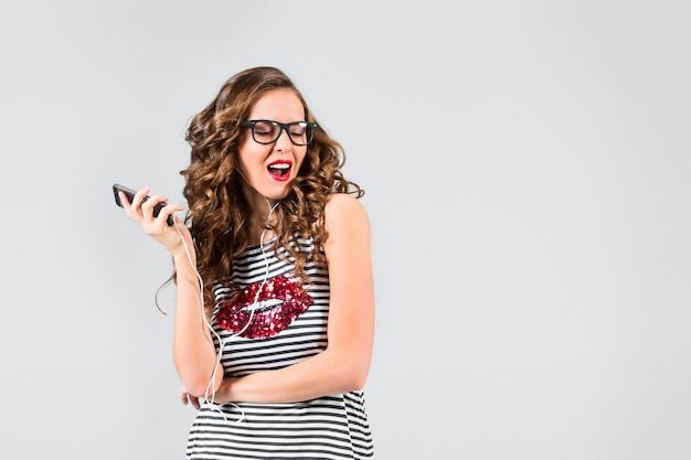 Gelukkige jonge vrouw die aan muziek met hoofdtelefoons luistert