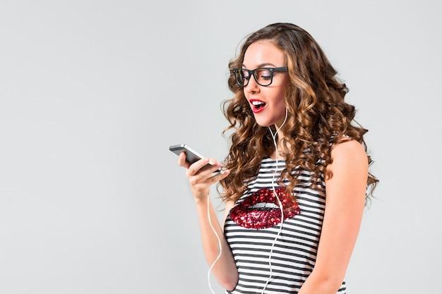 Gelukkige jonge vrouw die aan muziek met oortelefoons luistert