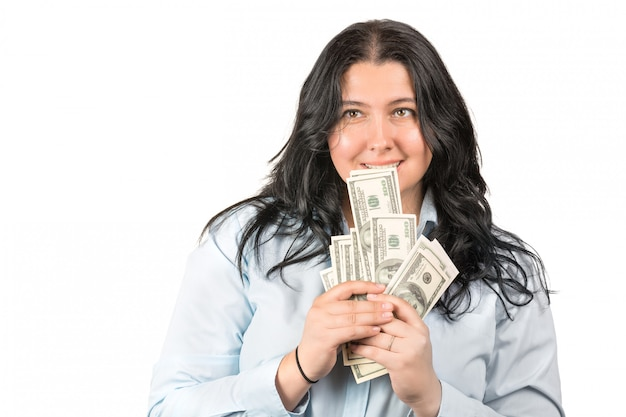 Gelukkige jonge vrouw die amerikaans die dollargeld in handen en mond houden op wit wordt geïsoleerd