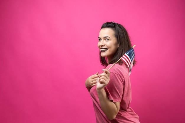 Gelukkige jonge vrouw die amerikaanse vlag houdt tegen een studio roze achtergrond