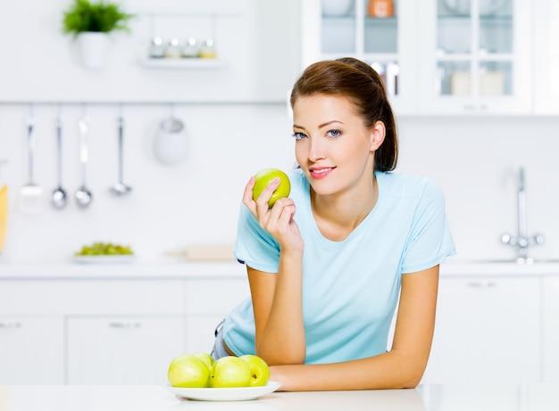 Gelukkige jonge vrouw die appels op keuken eet