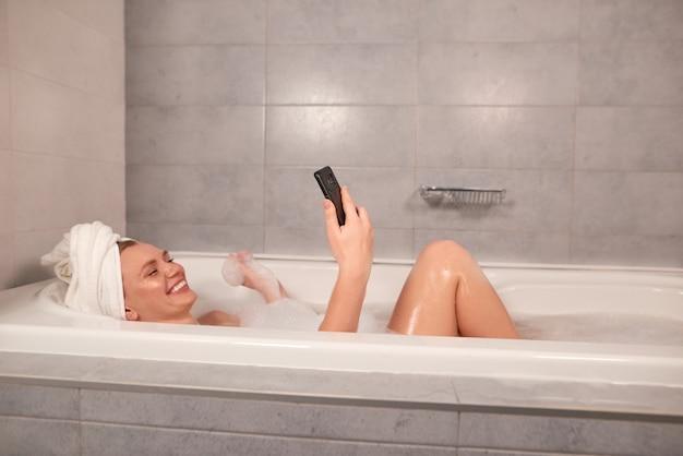 Gelukkige jonge vrouw die bad met schuim neemt en door videogesprek spreekt