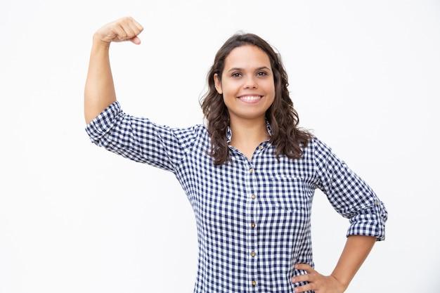 Gelukkige jonge vrouw die bicepsen toont