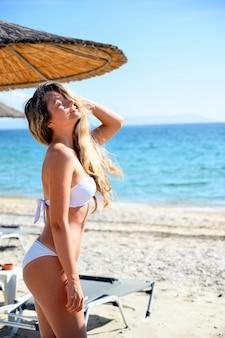 Gelukkige jonge vrouw die bij het strand in asprovalta, griekenland rust