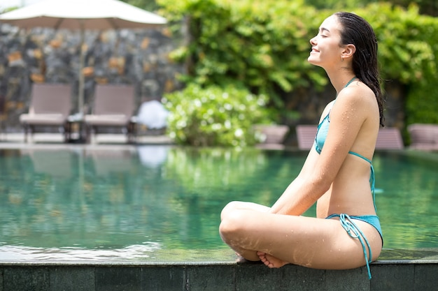 Gelukkige jonge vrouw die bij het zwembad van het hotel zit