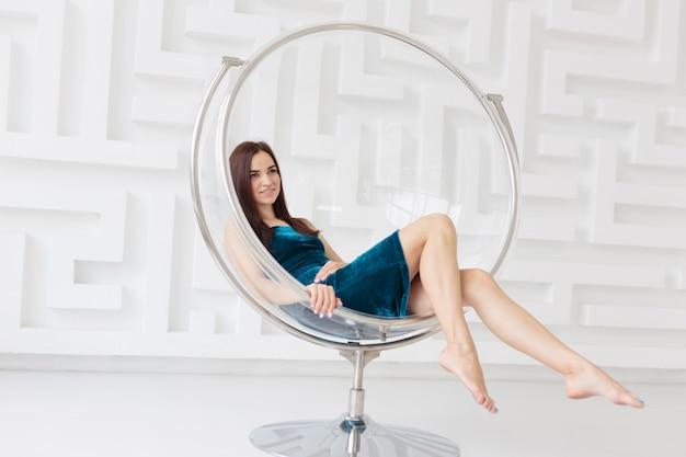 Gelukkige jonge vrouw die blauwe kledingszitting dragen die als ronde glasvoorzitter wordt ontspannen tegen witte muur