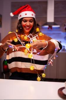 Gelukkige jonge vrouw die boom met lichten probeert te versieren