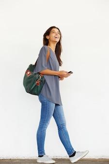 Gelukkige jonge vrouw die buiten met mobiele telefoon loopt
