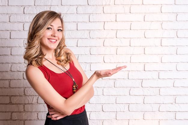 Gelukkige jonge vrouw die copyspace het richten tonen. blond jong wijfje dat vingers weg richt. kopieer ruimte voor uw tekst of advertentie-inhoud.