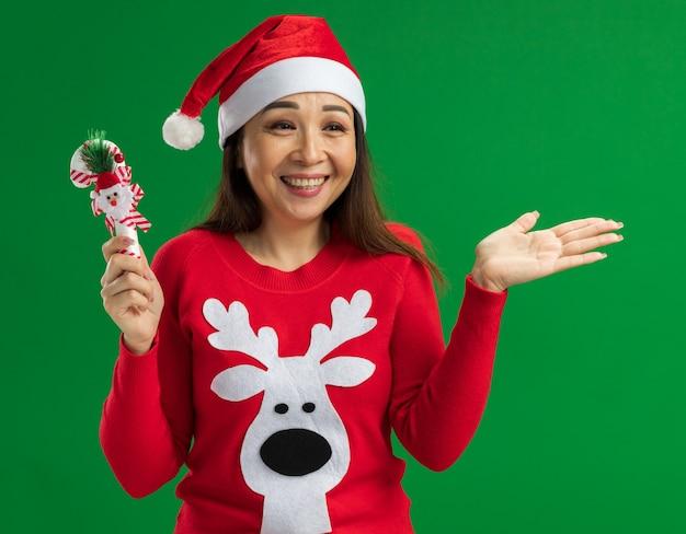 Gelukkige jonge vrouw die de hoed van de kerstmissanta en rode sweater draagt die het riet van het kerstmissuikergoed opzij kijkt met glimlach op gezicht die zich over groene achtergrond bevinden
