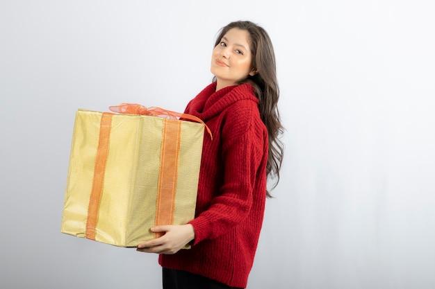 Gelukkige jonge vrouw die de huidige doos van kerstmis houdt.