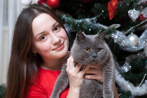 Gelukkige jonge vrouw die de kerstboom verfraait