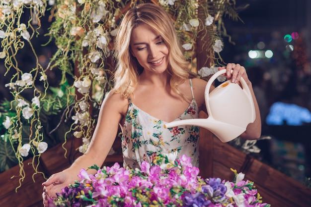 Gelukkige jonge vrouw die de verse bloemen in de tuin water geeft