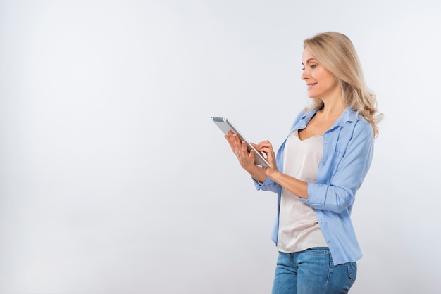 Gelukkige jonge vrouw die digitale tablet gebruikt die op witte achtergrond wordt geïsoleerd
